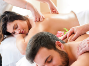 Couple laying on massage tables getting swedish massages together from therapist