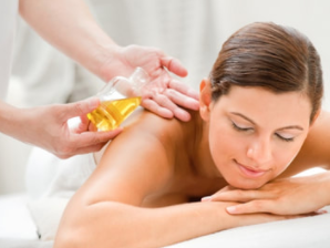 woman lying on massage table smiles as she gets an aromatherapy massage while therapist puts oil on her back
