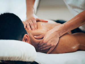 guy lying on table getting deep tissue massage on his neck and shoulders