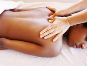 Woman laying on massage table getting deep tissue massage with thumbs pressing upper back area