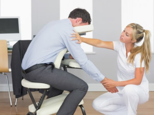 officer worker in business suit getting a mobile chair massage at his office