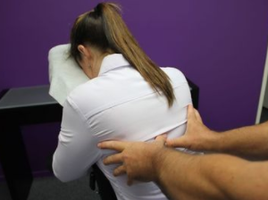 woman in massage chair wearing business clothes getting her back massaged at her office
